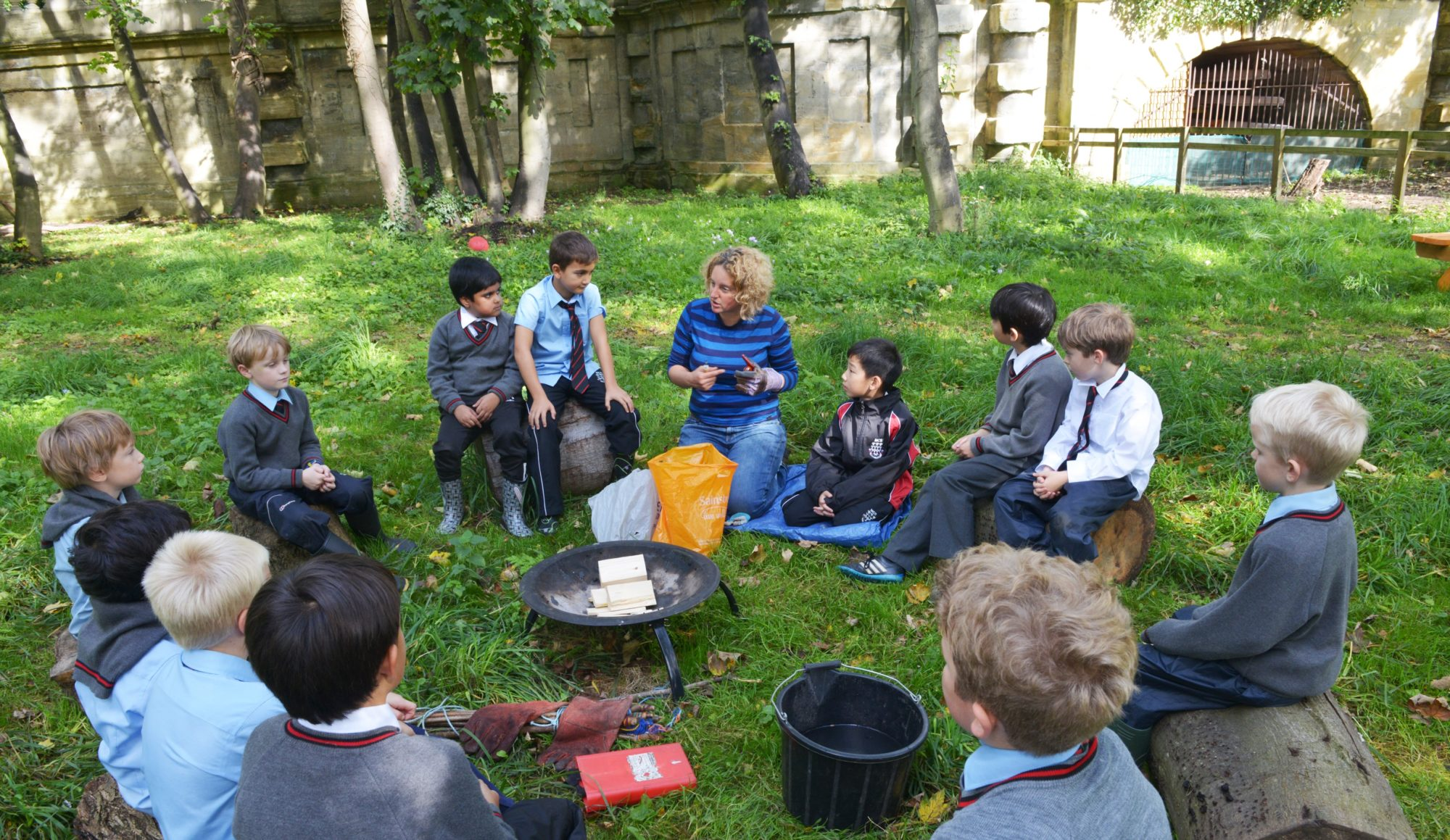 Magdalen College Junior School pupils sitting around a fire pit during Activities Afternoon