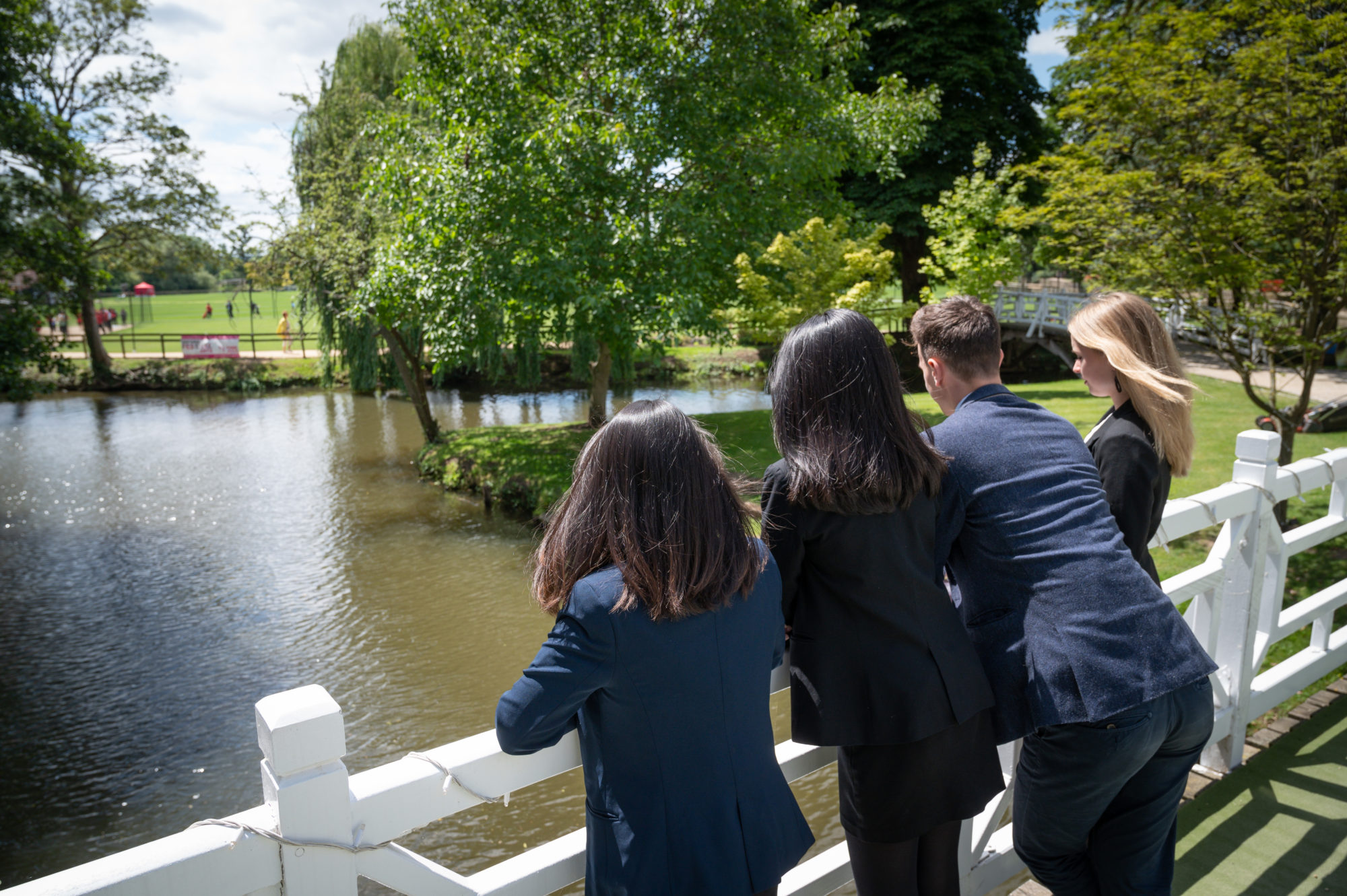 Magdalen College School Sixth Form pupils on white bridge over River Cherwell, Oxford