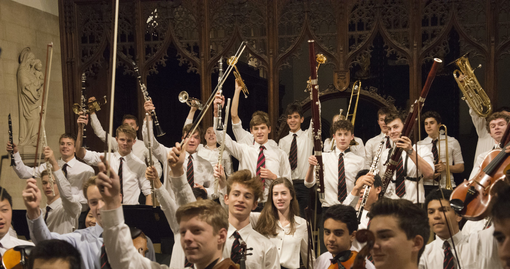 Magdalen College School pupils waving musical instruments in the chapel of St John the Evangelist Oxford