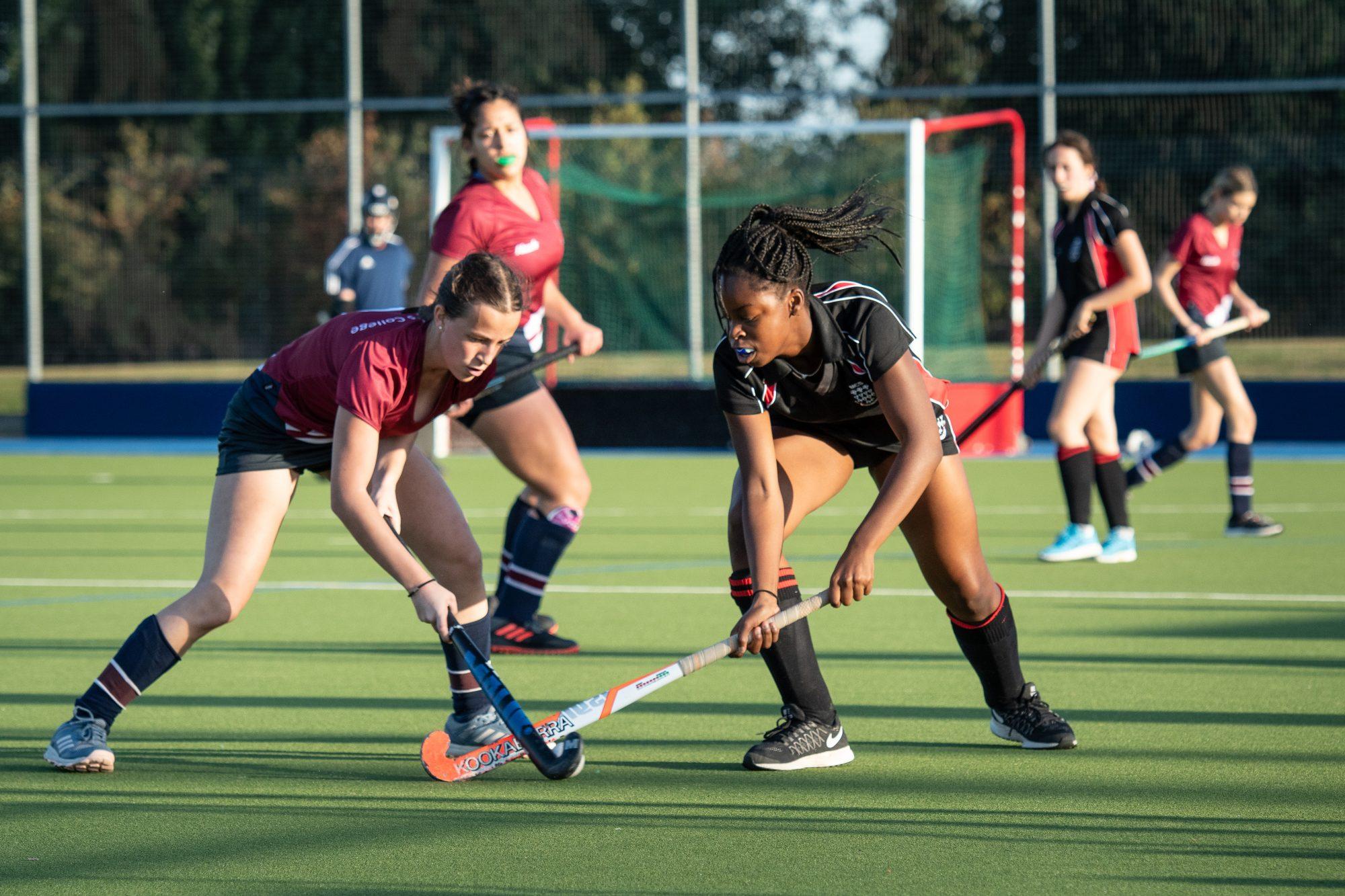 Magdalen College School Sixth Form pupils play hockey