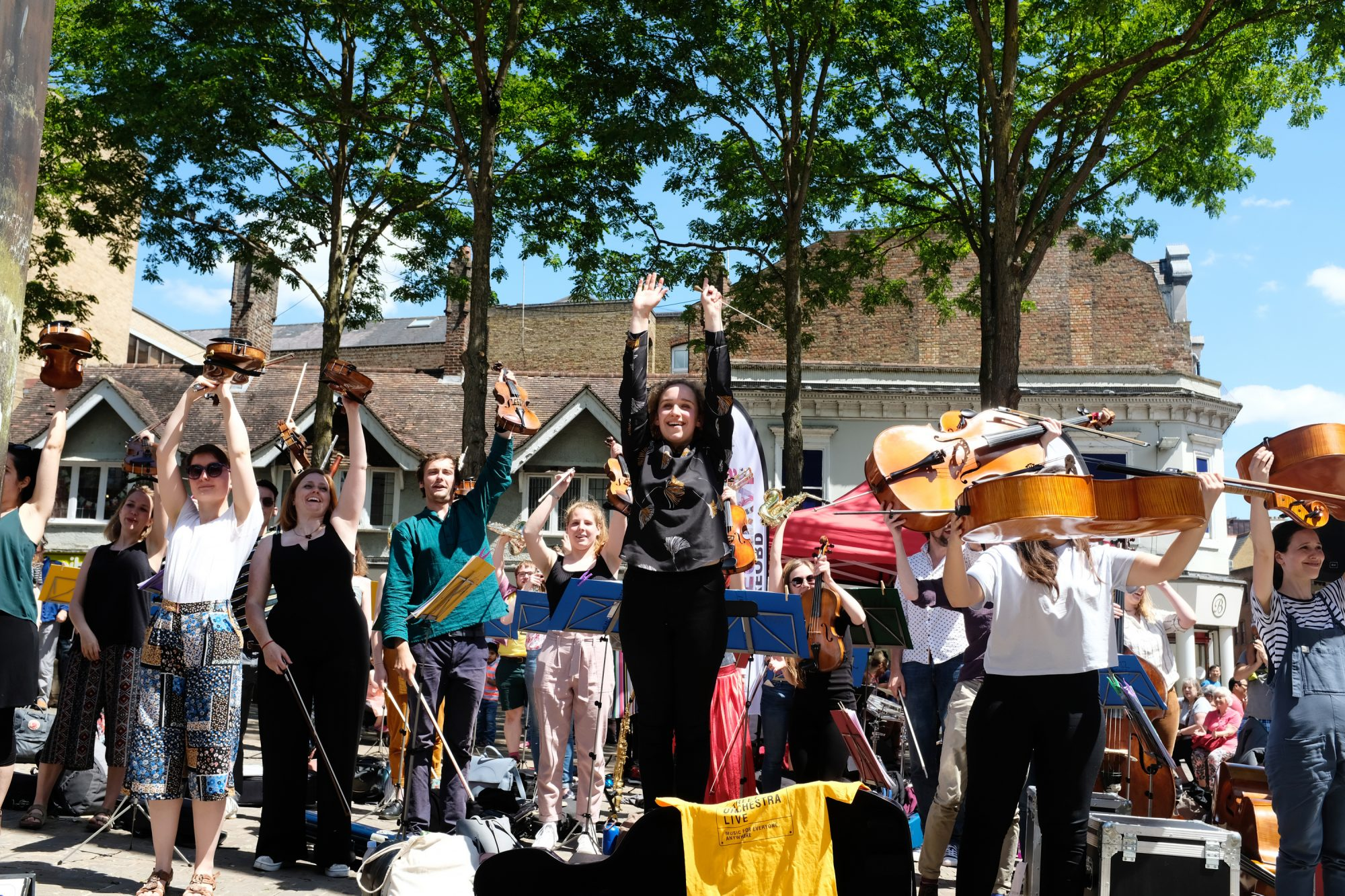 Members of Street Orchestra Live with their hands and instruments in the air during a live concert in Oxford's Bonn Square