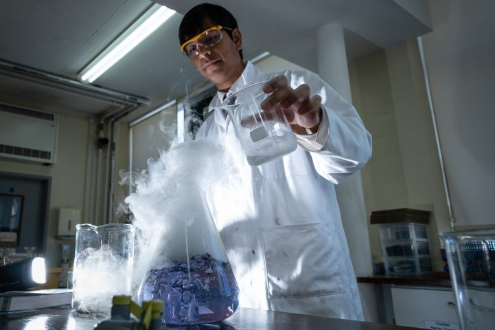 Magdalen College Pupil doing Chemistry experiment Pouring Clear Liquid Into A Conical Flask Creating A Bubbling Purple Liquid And Clouds Of Gas